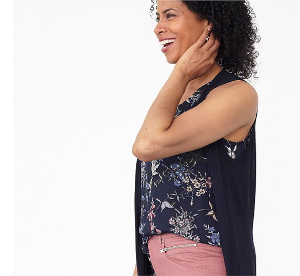 Model laughing wearing navy floral sleeveless blouse, pink jeans and navy sweater vest